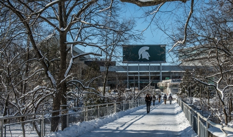Spartans trek across bridge behind the Main Library.