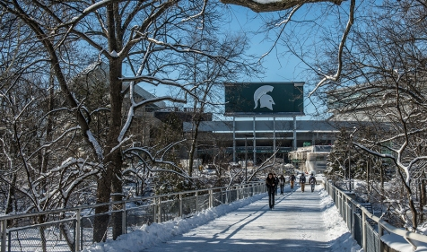 Spartans trek across bridge behind the Main Library.